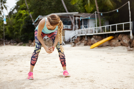 Caucasian woman jogger in sportswear having rest after long run, leaning over, placing elbows on her knees. Female runner in pink sneakers resting and recovering after physical exercise at seaside Stock Photo