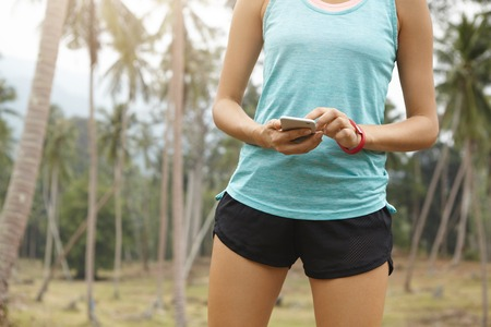 newsfeed: Midsection of Caucasian female athlete wearing blue top and black shorts checking newsfeed on social networks using her mobile phone while having rest after long run in tropical forest. Horizontal