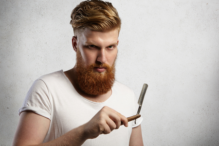 Redhead hairdresser or barber with fuzzy beard dressed in white t-shirt demonstrating sharp blade of his straight edge razor in barbershop, ready to shave his clients. Studio shot on white background Stock Photo