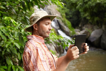 People and technology concept. Side view of bearded ecologist in panama hat taking photographs or shooting video of wild nature in tropical forest using digital tablet, standing at mountain river Stock Photo