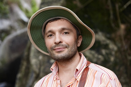 field work: Good-looking botanist exploring wildlife of rainforest in tropical country, working on scientific study. Male ecologist in striped shirt and hat studying environmental problems at field work