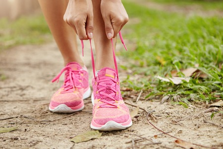 Cropped view of female runner with slim athletic legs lacing pink running shoes, getting ready for jogging exercise in woods. Sporty woman tightening laces of her sneakers, preparing for morning jog Stock Photo