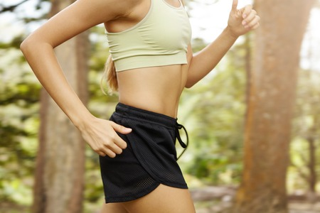 Cardio running workout. Upper body cropped shot of unrecognizable woman runner in fast motion showing sports bra and black shorts against green forest background. Mid section of fit female torso Stock Photo
