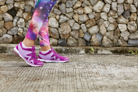 working out: Close up image of violet female running shoes during outdoor training. Cropped portrait of woman athlete jogging on tiled pavement wearing cosmic print sportswear. Girl working out in open air