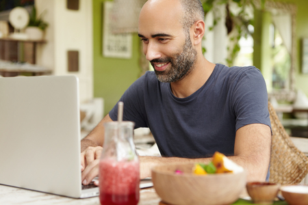 Adult bearded man having breakfast at cafe, sitting at table in front of generic laptop and looking with smile while messaging friends via social networks, enjoying free wi-fi. Selective focus Stock Photo