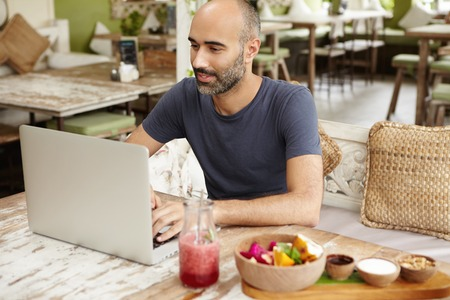 Happy man typing message on laptop while having fresh smoothie at sidewalk restaurant. Smiling freelancer dressed casually using wireless internet connection for distant work, resting at cafe Stock Photo