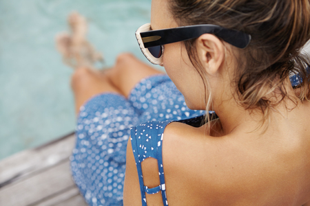 submerging: Outdoor portrait of attractive future mother in stylish glasses and summer dress, sitting on edge of swimming pool with her legs submerging in water, refreshing herself on hot weather. View from back