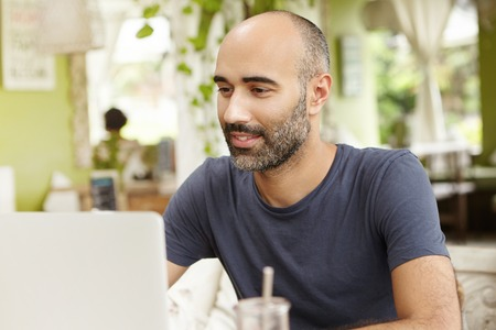 Hardworking man with inspired smile looking at screen of his generic laptop while watching video online. Happy male browsing internet using notebook, sitting at cafe with green interior background
