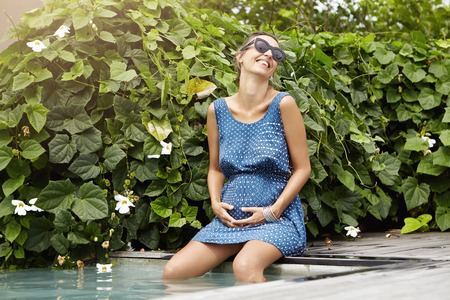 submerging: Happy pregnancy and maternity concept. Beautiful expectant mother in sunglasses with hands on her belly having fun and laughing while refreshing herself at swimming pool, submerging her legs in water Stock Photo