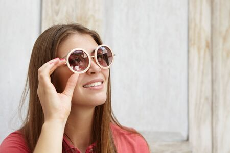 them: People and lifestyle. Pretty woman with long fair hair posing against wooden wall, wearing round sunglasses with mirror lenses, adjusting them while looking at something with happy joyful smile