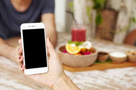 Young female using smart phone while having lunch at cafe. Caucasian woman holding electronic device with blank screen with copy space for your promotional content. Selective focus on mobile