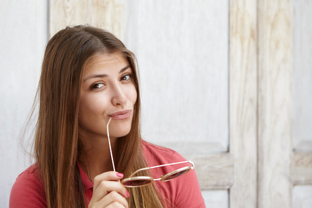 Happy and joyful young Caucasian female with long hair pouting her lips, holding shades and touching lips with temple tip, having flirting and mysterious look, posing isolated at wooden background
