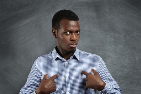 Headshot of young dark-skinned man pointing at himself, making excuses or verbally defending, having perplexed and puzzled look as if saying: Who me? Human face expressions, emotions and feelings