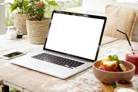 Laptop en andere elektronica op werkruimte. Bedrijfswerkplaats met modern open laptop model en slimme telefoon op houten lijst. Leeg wit scherm met kopie ruimte voor uw ontwerp, tekst of inhoud