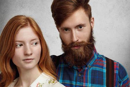 modelos posando: Tiro del estudio de la hermosa joven pareja de pie cerca uno del otro. Hombre hermoso con la barba con estilo difuso abrazando a su novia hermosa pelirroja que mira lejos con expresión de la cara en cuestión