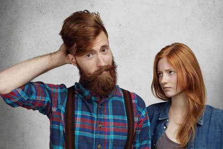 desprecio: hombre con barba y mirada confusa y culpable, rascándose la cabeza mientras que su novia pelirroja de pie junto a él y mirando con desprecio y disappointement. hombre y una mujer que tienen pelea