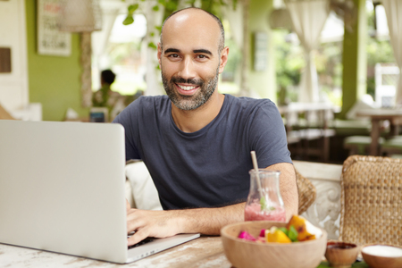 Bearded businessman dressed casually checking email on his laptop during breakfast, sitting at nice cafe, drinking smoothie, looking at camera with happy confident face expression, enjoying vacations