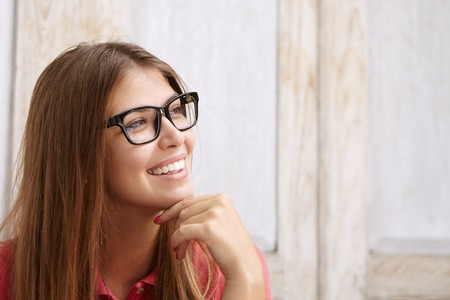 loose hair: Close up view of young happy beautiful female with loose hair wearing stylish spectacles and looking ahead of her with thoughtful and inspired smile, touching her chin while dreaming of something