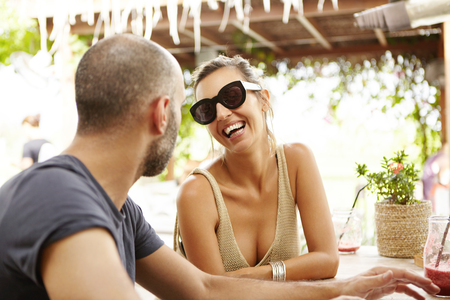 sidewalk talk: Couple of tourists resting at outdoor restaurant. Travelling people eating healthy food together at lunch during holidays. Beautiful woman in sunglasses drinking smoothie at sidewalk cafe with friend