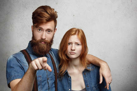 Portrait of displeased or angry man with stylish beard pointing at camera and hugging protectively beautiful redhead woman with hurt look, defending his girlfriend and warning you not to touch her