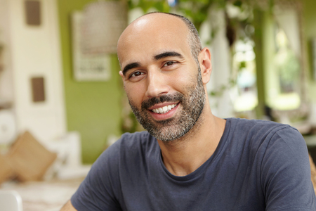 People and lifestyle concept. Happy middle-aged unshaven man wearing casual t-shirt looking at camera with cheerful smile while having lunch at outdoor cafe sitting against green interior background Banco de Imagens