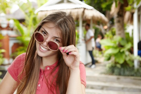 loose hair: Beautiful lady with long loose hair taking off her round sunglasses and looking at camera with happy and joyful smile while having nice time outdoors during holidays. Young woman holding stylish shades Stock Photo