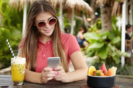 newsfeed: People, leisure, technology and communication. Young lady with beautiful long hair holding smart phone, typing message or checking newsfeed having fresh drink during breakfast at outdoor bar
