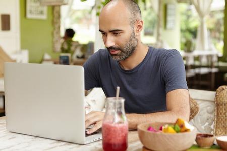 Baard middelbare leeftijd zelfstandige man zit in cafe voor generieke laptop en kijken naar scherm met ernstige en geconcentreerde expressie tijdens het werken op afstand op zijn project, met behulp van gratis wifi