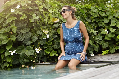 Stylish happy young pregnant woman in dark shades relaxing outdoors at swimming pool, her legs dangling in blue water, enjoying hot summer days and smiling cheerfully. Pregnancy and maternity concept