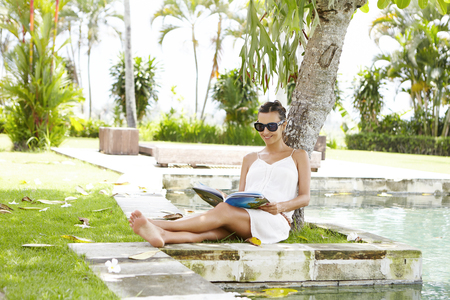 female magazine: Young mother expectant wearing shades having rest under tree with magazine in her hands during vacations in tropical country. Happy pregnant female relaxing near swimming pool in hotel garden Stock Photo