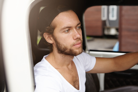 Close up view of attractive young bearded man in snapback sitting inside cabin of his white car, going to see his parents in small town but looking sad and tired while being stuck in traffic jam Stock Photo