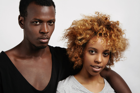 nosering: People, love and relationships. Stylish dark-skinned couple having rest indoors, looking at camera. Fashionable man in black scoop neck t-shirt hugging his beautiful girlfriend with nose-ring Stock Photo