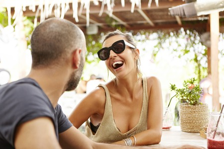sidewalk talk: People and lifestyle concept. Outdoor shot of woman in stylish shades laughing at jokes of bearded man during date, relaxing at cafe on sunny day. Beautiful couple enjoying nice talk, having drinks Stock Photo