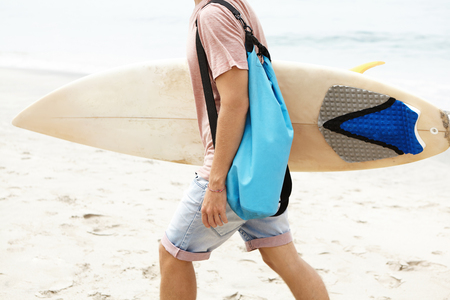 Hobby, active lifestyle and summer vacations concept. Cropped shot of young tourist with bag walking along sandy beach, carrying his white bodyboard under his arm before surf ride on windy day