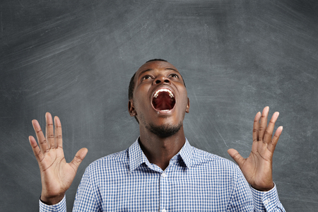 Oh no! Mad dark-skinned man in checkered shirt shouting, throwing his head back and gesturing in desperation as if he failed important deal. Annoyed furious teacher yelling and calling for silence