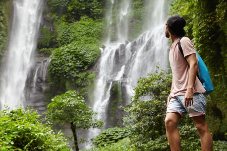 waterfall model: People, wildlife and adventure concept. Fashionable young adventurer with backpack contemplating waterfall landscape. Male tourist enjoying beautiful nature around him during his journey in rainforest
