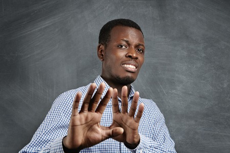 defend: African man with scared expression on his face making frightened gesture with his palms as if trying to defend himself from someone. Fearful dark-skinned man asking to stop, gesturing with his hands