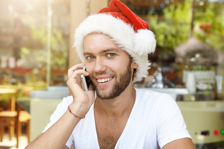 fiestas electronicas: Cheerful young Caucasian businessman in Santa Claus hat having phone conversation, using electronic device, wishing Merry Christmas and Happy Holidays to his family while relaxing at corporate party