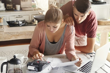 Family budget and finances concept. Young serious wife and husband doing accounts together at home, planning new purchase: woman holding document and making necessary calculations on calculator Banco de Imagens
