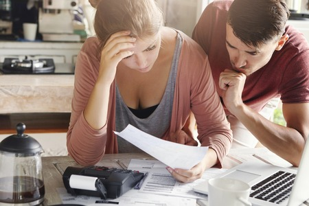 Young couple calculating their domestic budget together in kitchen, trying to save money for buying new car, having stressed and frustrated looks. Unhappy woman showing unpaid bill to her husband