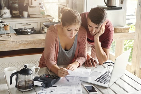 Young stressed family paying utility bills online using laptop. Worried woman holding document, calculating domestic expenses together with her husband, sitting at table with papers and calculator