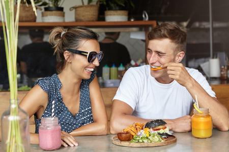 Caucasien couple ayant une belle conversation, se regardant et riant pendant le déjeuner au café. Homme mangeant des frites et parlant à sa petite amie à lunettes, qui sourit joyeusement Banque d'images - 68373243