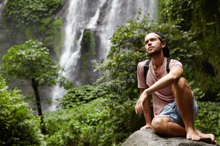 People, nature and adventure. Young hipster with backpack sitting on big rock by waterfall on background, having joyful look. Stylish barefooted hiker relaxing on stone during journey in jungle Stock Photo