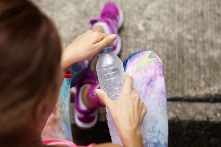 dehydration: Stylish young female athlete in sportswear holding plastic bottle of drinking water, opening it, preventing dehydration while sitting outdoors after active workout. Selective focus on womans hands Stock Photo