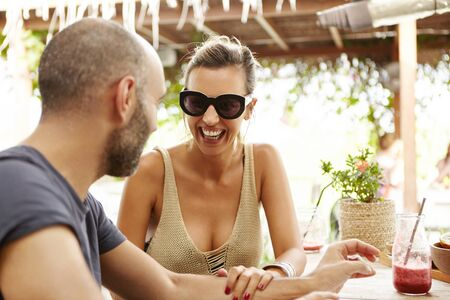 sidewalk talk: Happy female wearing sunglasses and top with low neck sitting at outdoor cafe with handsome man, touching his arm and laughing. Cute couple spending time together during vacations. Film effect