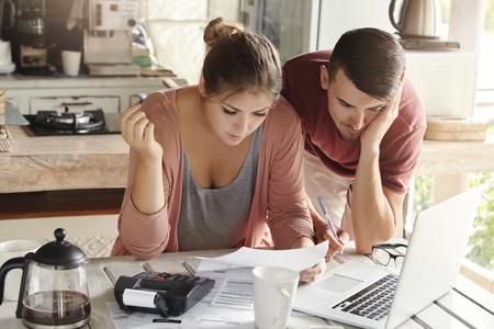 matrimonio joven con muchas deudas haciendo papeleo juntos, revisar sus cuentas, la planificación de presupuesto familiar y el cálculo de las finanzas en la mesa de la cocina con los papeles, la calculadora y el ordenador portátil