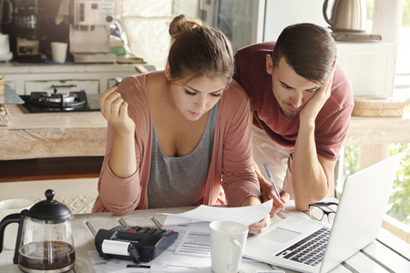 Young married couple with many debts doing paperwork together, reviewing their bills, planning family budget and calculating finances at kitchen table with papers, calculator and laptop computer Фото со стока