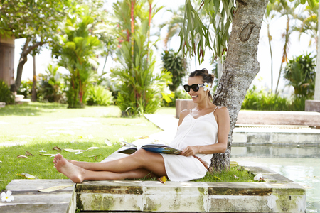 Young Caucasian pregnant female in stylish shades hiding from sunshine in shadow under tree, smiling happily while reading magazine. Happy woman expecting baby enjoying vacations at health resort Stock Photo