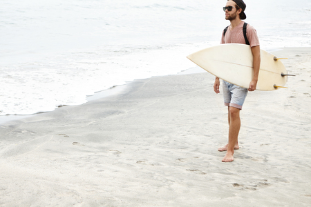 People, leisure and travel concept. Rear view of barefooted surfer wearing sunglasses and backpack walking along beach, holding white surfboard in his hand, looking for waves for surfing on sunny day Stock Photo