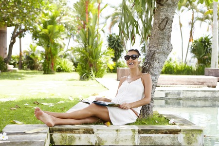 female magazine: Pregnancy and maternity concept. Attractive pregnant female with cheerful smile wearing sunglasses and flower in her hair sitting in shadow of big tree and having rest, reading womens magazine